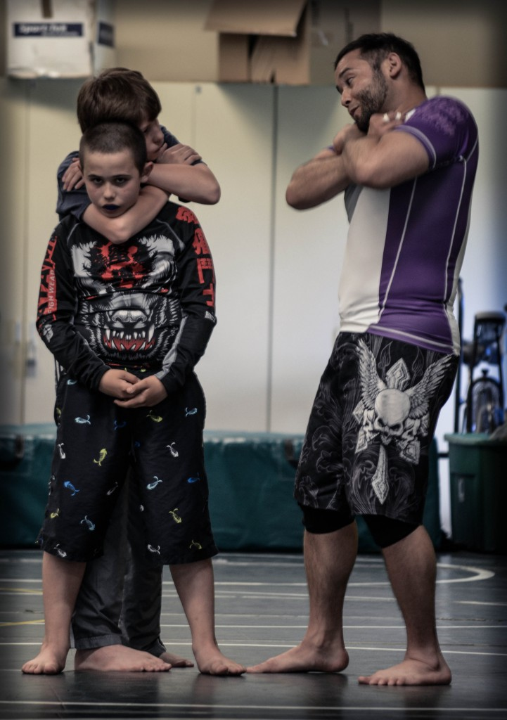 Coach Pipes showing Ethan Highfill how to finish a rear-naked choke