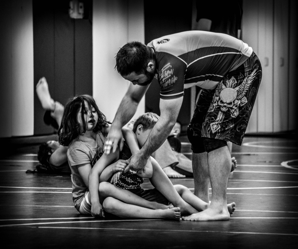 Coach Pipes helping Naomi complete an armbar from the back