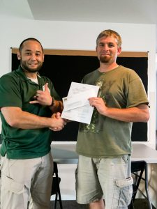 Jeremy Seda receiving a check from Russ Harrington to finalize the fund-raising for Quincy BJJ's mat purchase.
