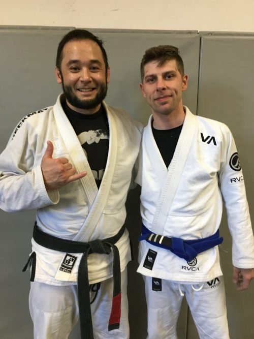 Professor Jeremy Seda standing next to Devon, Getting an Upgrade on His Blue Belt